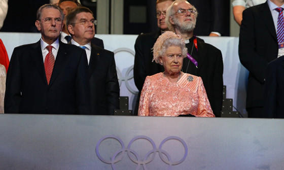 IOC President Jacques Rogge (far left) and the favorite to be his successor, Thomas Bach of Germany (to Rogge's immediate right) with Queen Elizabeth II at the opening ceremony of the 2012 London Olympics.  (Cameron Spencer / Getty Images)