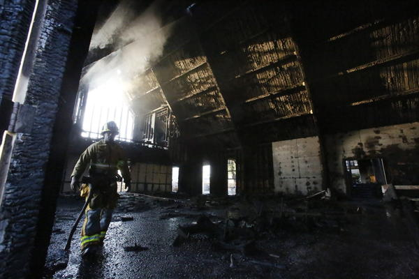 A Los Angeles firefighter walks through what's left of the Bethesda Temple Church on Crenshaw Boulevard after an early morning blaze gutted the interior.