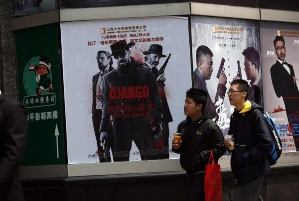 "Chinese students walk past a movie poster of ""'Django Unchained"" in Shanghai, China. After mysteriously vanishing from Chinese theaters two weeks ago, the Quentin Tarantino film will soon return."