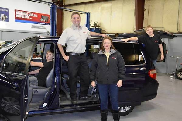 Matt and Laura Weber of Clark&'s Car Care pose with sons, Parker, 14, in the driver's seat and Trent, 12.