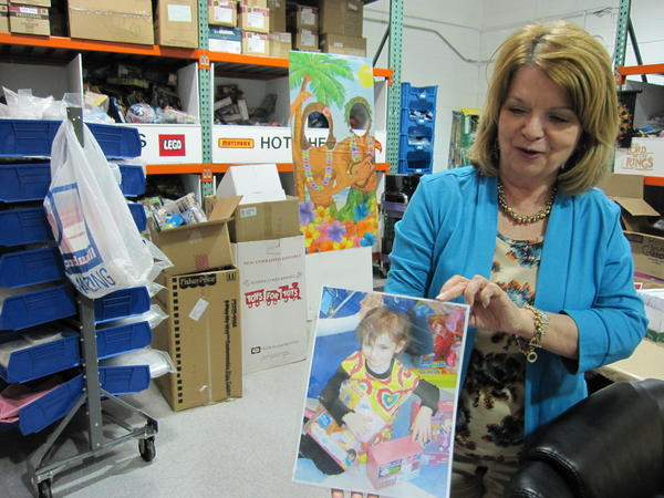 Colleen Kisel of the Pediatric Oncology Treasure Chest Foundation with a photo from a recent treasure chest opening in St. Louis.