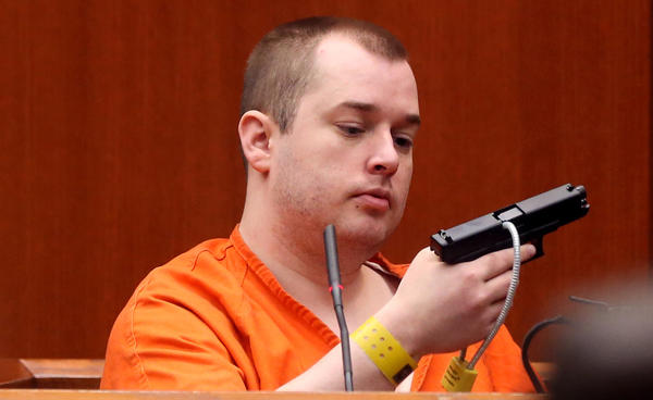 During cross-examination, Jacob Nodarse holds the gun used to shoot and kill Michael Kramer, 20, and Kramer's parents, Jeffrey, 50, and Lori, 48. Nodarse is testifying at the trial of Johnny Borizov at the DuPage County Courthouse in Wheaton. Prosecutors contend that Borizov, who is charged with murder, conspiracy and solicitation, pressured Nodarse to commit the shooting.