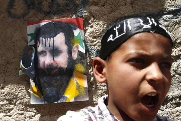 A boy shout slogans as a shoe hangs on the picture of Syria's President Bashar al-Assad behind him during a protest against al-Assad after Friday prayers in Raqqa province, east Syria.