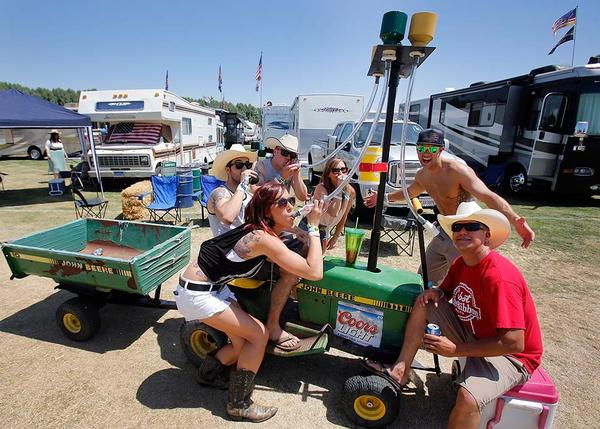 "Country music fans. from left, Santi Pena, Ashlee Knight, John Gruttadaurio, Nicole Canterbury, Steven Worell and Kimbo Katsuda show off their popular  ""John Beere beer bong tractor"" before listening to bands on the first day of the Sta"