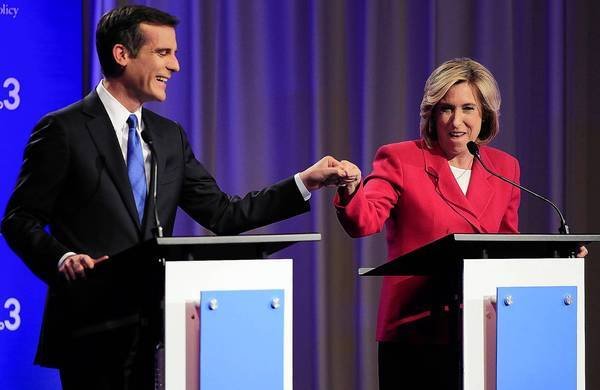 Los Angeles mayoral candidates Eric Garcetti and Wendy Greuel bump fists before they square off in a debate at USC earlier this week.
