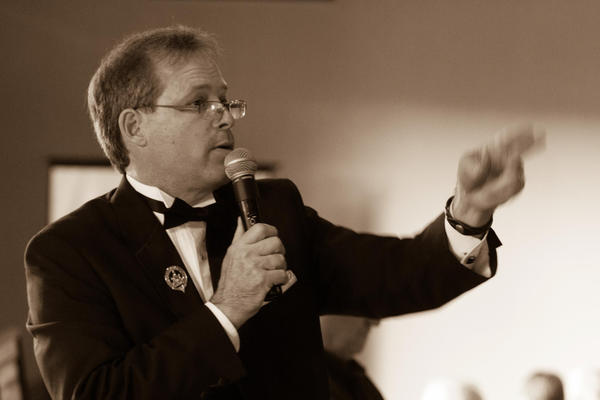 Auctioneer Scott MacKenzie often lends his services to local charity events, like the annual Bergmann Center fundraiser. Here he runs an auction to benefit the Great Lakes Chamber Orchestra.