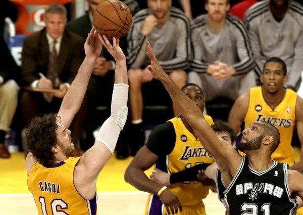 Lakers power forward Pau Gasol attempts a shot over the challenge of Spurs power forward Tim Duncan.