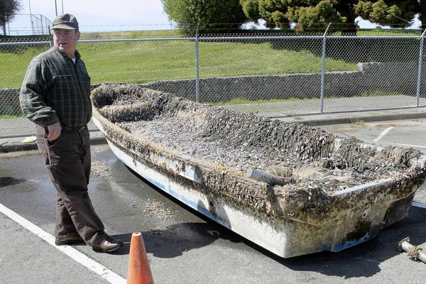 Troy Nicolini of the National Oceanic and Atmospheric Administration's National Weather Service inspects the Japanese boat that washed up in Crescent City.