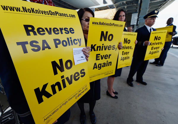 LOS ANGELES, CA - APRIL 01: American Airlines employee Anita Vaccaro (L) holds a sign as she protests in front of Tom Bradley International terminal in opposition to the FAA's recent decision to start allowing small pocket knives back on board jetliners on April 1, 2013 in Los Angeles, California. The Federal Aviation Administration said the relaxing of the pocket knife ban will help TSA agents to look out for more serious items, such as expolsives and guns.
