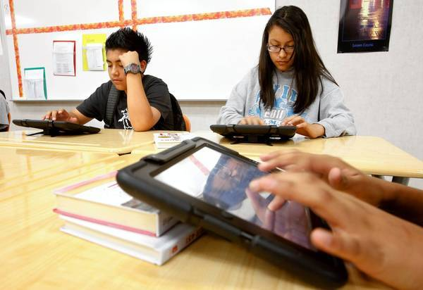 Bryan Acevedo, 15, and Elizabeth Varela, 14, along with other students, use their iPads while working on an assignment in their ninth-grade English class at Valley Academy of Arts and Sciences in Granada Hills, one of the first L.A. Unified schools to provide students with iPads under a pilot program.