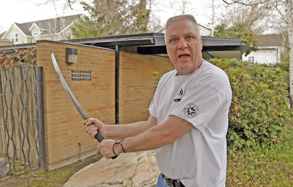 Kent Hendrix, 47, wields his sword near his house in Salt Lake City. Hendrix, a Mormon bishop, came to the aid of a woman who was being attacked in front of his house.