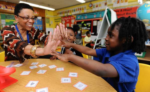 Lauren Preston, a Mary Ann Winterling Elementary pre-kindergarten teacher, congratulates (right) Samonte' Reid, 4, as they work on numbers and sets. Niy'shei Whitaker, 4, center, watches.