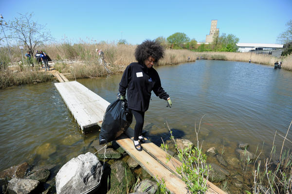 Asia McCallum, 17, Baltimore, a member of Aquarium On Wheels, carries a bag of trash across a floating bridge.
