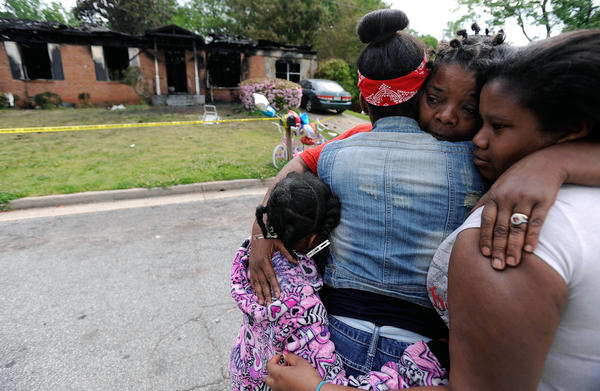 Family members and neighbors console each other following a house fire that killed four children and their mother in Newnan, Ga. The children's older sister, 11, was the only survivor.