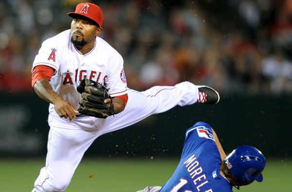 Angels second baseman Howie Kendrick completes a double play while avoiding the slide of Rangers first baseman Mitch Moreland during a game last week.
