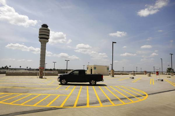 A truck sits parked among empty parking spaces at terminal top parking as an airplane takes off at Orlando International Airport on April 2, 2013. (Jacob Langston/Orlando Sentinel)