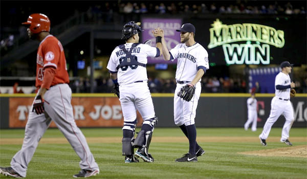 Howie Kenrick walks off the field as closer Tom Wilhelmsen and catcher Jesus Montero celebrate the Mariners' win over the Angels, 3-2.