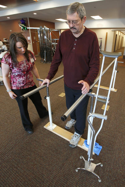 Tim Brown, of Ellendale, walks between parallel bars under the supervision of Daydrea Nelson, a physical therapist assistant with Avera St. Luke's, left, at therapy session Wednesday. Brown, who was paralized from the neck down as a result of West Nile Disease last summer, has made great strides in his recovery. American News Photo by American News Photo by John Davis