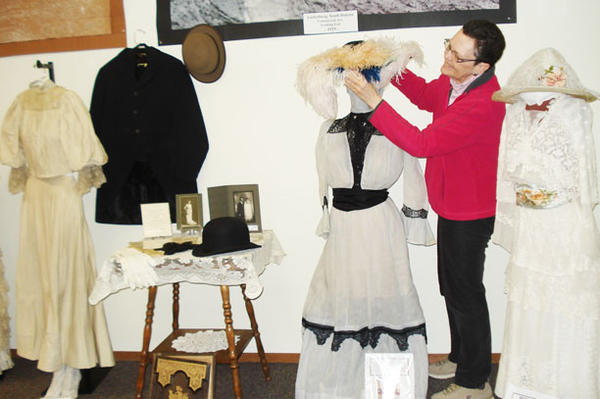n engagement dress with an ostrich-feathered hat is part of the display at the Dakota Sunset Museum in Gettysburg. Shown in the photo is Kathleen Nagel of the museum.