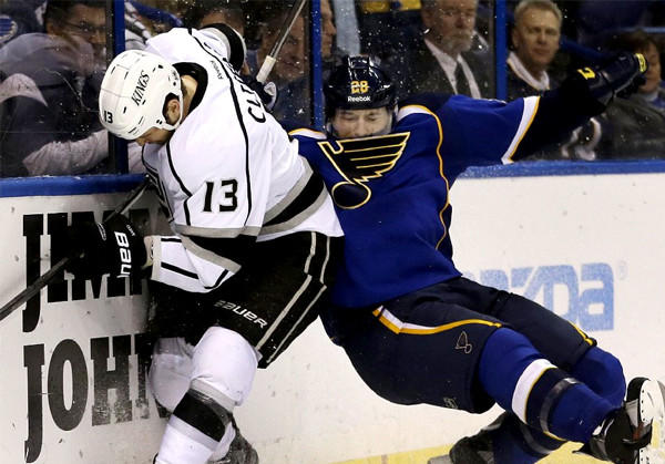 The Kings' Kyle Clifford, left, slams the St. Louis Blues' Ian Cole against the boards as they battle for a loose puck back in February.