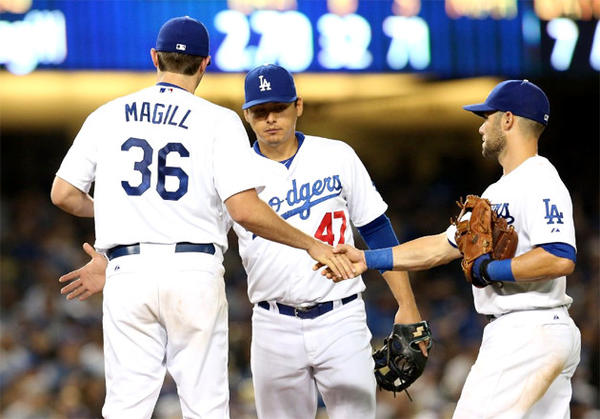 Dodgers pitcher Matt Magill is congratulated by Luis Cruz (47) and Skip Schumaker as he is removed from the game in the seventh inning after his first major-league start.