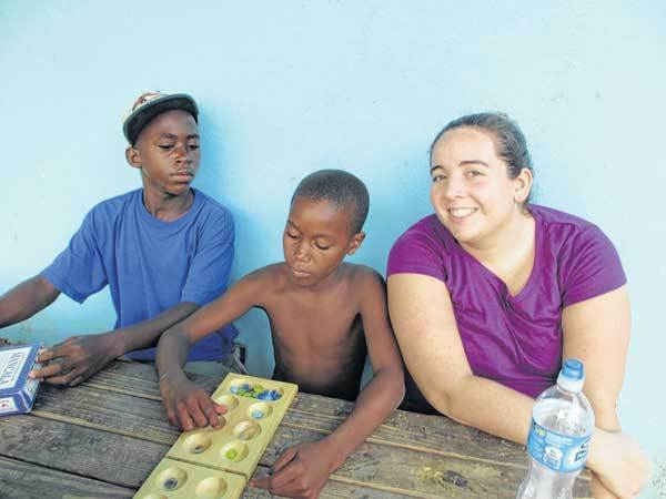 Rachel Stanley, a member of Christ the King Lutheran Church, plays a board game with youths from the Sunbeam Boys Home in Jamaica.