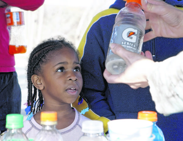 Grace Hetler, 5, watches as a bottle of a homemade sports drink is shaken Saturday at the Healthy Kids Day activities at the Michiana YMCA. Families had the chance to learn about healthy activities in a variety of areas.