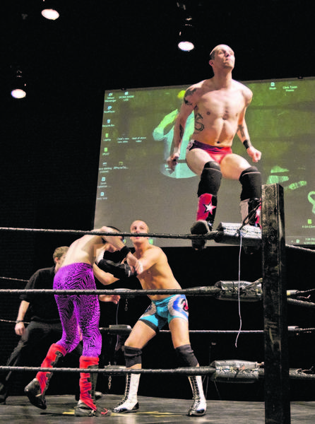 "Wrestler Andy Haley, known as ""Jonny Crisis,"" right, prepares to do a backflip off the ropes and onto Justin Haley, known as Just-N-Sane, left, and Jack Verville during the Outlaw Wrestling match at the Century Center on Saturday, in South Bend."