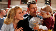 Loyola men's coach Shane Davis, wife Andrea and daughter Sydney with the Midwest Intercollegiate Volleyball Association trophy the Ramblers won Saturday night. (Steve Woltmann/ Loyola Athletics)