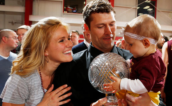 Loyola men's coach Shane Davis, wife Andrea and daughter Sydney with the Midwest Intercollegiate Volleyball Association trophy the Ramblers won Saturday night.