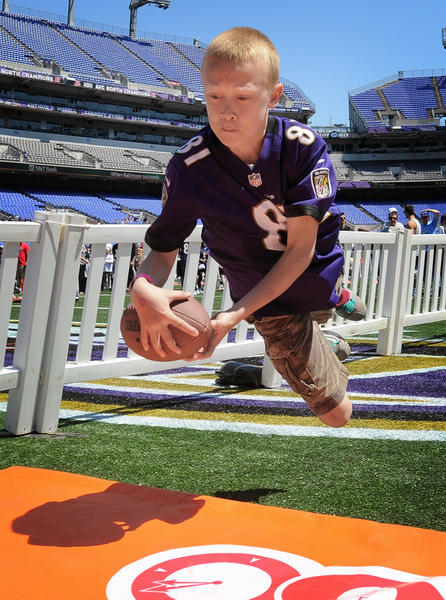Ravens fan Bradley Knisely, 10, of Fredericksburg, Va., makes a diving football catch during field drills.