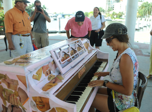 "Kami Wilson of Ft. Lauderdale pounds out ""Chopsticks,"" on one of four painted pianos at the Esplenade Park in downtown Ft. Lauderdale, Sunday, April 29, 2013. The City of Fort Lauderdale and Riverwalk Fort Lauderdale have partnered with Cadence, a downtown based Landscape Architecture and Urban Design firm to collaborate on this public art and music installation. Joe Cavaretta, SunSentinel (c)2013"