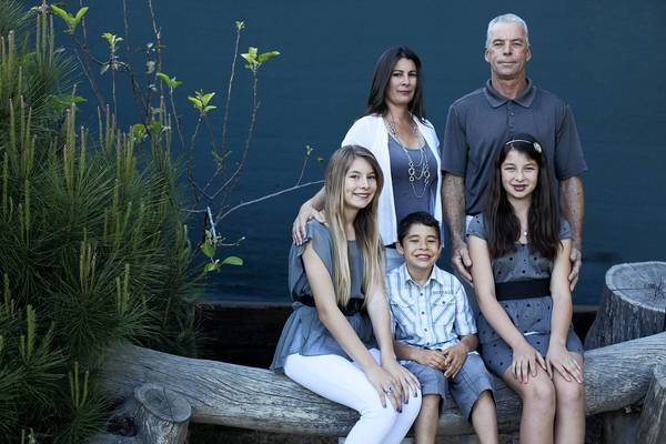 Carol and Daniel Vos pose with their children, Danielle, 13, left, Philip, 9, and Hannah, 11, at their home in Long Beach. The Voses want to adopt the daughter of another of Daniel's sons but say that Los Angeles County's delay in processing their paperwork has hurt their chances.