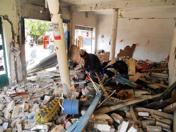 A Pakistani man looks at debris in the destroyed office of an election candidate after a bombing in the city of Kohat.