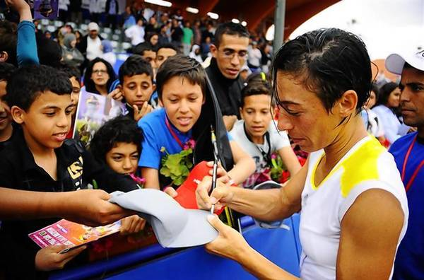 Schiavone of Italy signs autographs for fans after defeating Dominguez Lino of Spain in their women's singles final tennis match of the Marrakech Grand Prix.