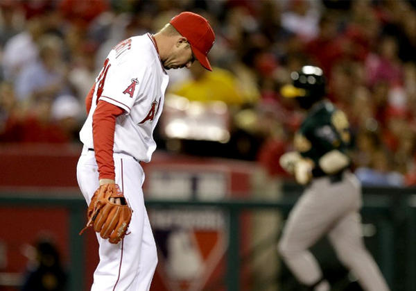 Angels relief pitcher Sean Burnett looks down as Oakland Athletics' Yoenis Cespedes rounds the bases after hitting a home run.