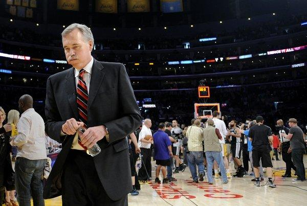 Coach Mike D'Antoni leaves the court after the Lakers were swept out of the playoffs by the Spurs with a Game 4 loss on Sunday.