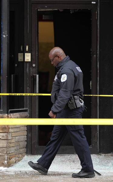 A Chicago police officer investigates the shooting in the 2500 block of West Division Street in Chicago on Sunday.