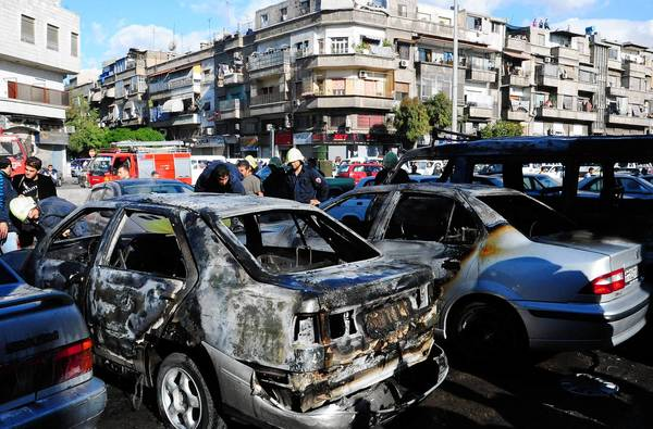 Syrians assess the damage after a bomb explodes near a bakery in the capital, Damascus. Middle-class professionals who once thought the city relatively safe from clashes between rebels and government forces are leaving.
