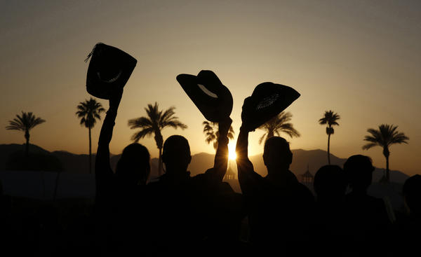Fans are silhouetted at sunset as they cheer for Dwight Yoakam's performance on the Palomino Stage.