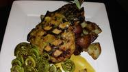 Pork chop with fiddlehead ferns at Regi's