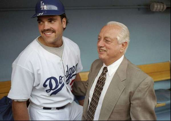 Mike Piazza stands with Tommy Lasorda in the Dodgers dugout in 1997.