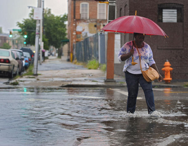 A pedestrian walks through the water while crossing Aliceanna Street, getting her feet wet from the aftermath of a severe downpour that resulted in flash flooding in Fells Point in September 2012.