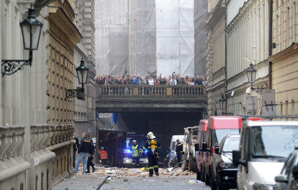Firemen stand in front of a building damaged in a blast by on April 29, 2013 in Prague, Czech Republic.