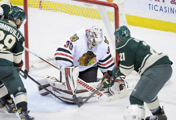 Ray Emery #30 of the Chicago Blackhawks stops the shot by Kyle Brodziak #21 of the Minnesota Wild during the third period of the game on April 9, 2013 at Xcel Energy Center in St Paul, Minn.