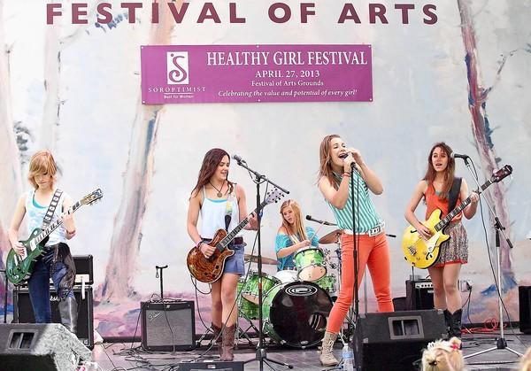 Orange County's Yours Truly band members, from left, lead guitarist Sydney Boodman, rhythm guitarist Shea Hamilton, drummer Lauren Borden, lead singer Chloe Fry and bass guitarist Kayt Christensen perform during the Healthy Girl Festival at the Festival of Arts grounds on Saturday. The event was hosted by the Soroptimist International of Laguna Beach.