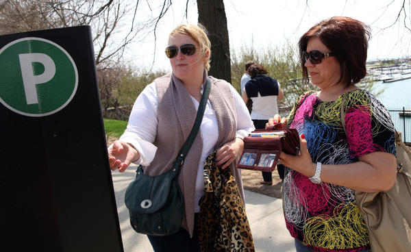 Dorothy Kawula, of Chicago, and her cousin Iwona Karpel, of Toronto, feed the meter box across from the Shedd Aquarium today.