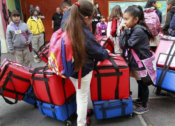 Students at Figueroa Street Elementary School prepare to cart breakfast, packed in insulated cartons, to the classroom.