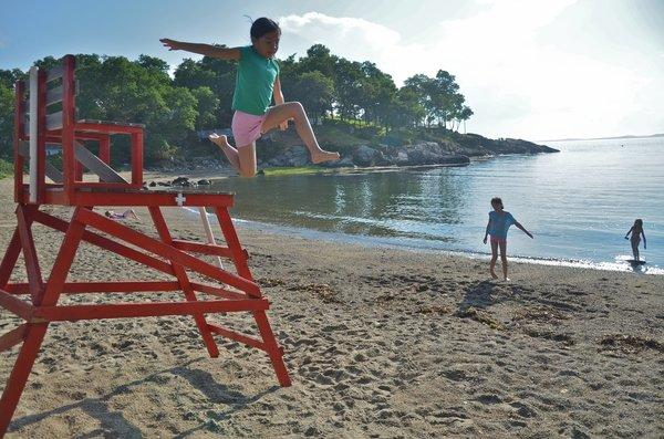 This was a sunny summer day in Plum Cove on Cape Ann, but the water was still pretty cold. So my daughter found an idle lifeguard chair and put it to use as a launching pad. Taken in 2012.