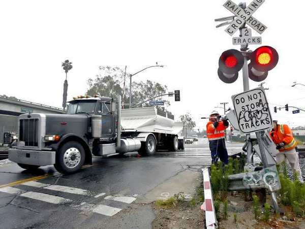 Metrolink workers repair a broken railroad crossing arm at the tracks on Doran St. and San Fernando Road in Glendale.
